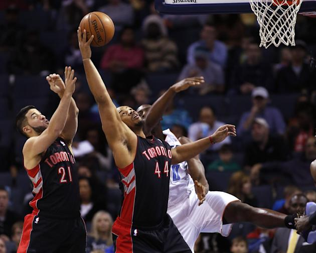 Toronto Raptors guard Greivis Vasquez, of Venezuela (21). and forward Chuck Hayes (44) battle Charlotte Bobcats center Bismack Biyombo, of the Democratic Republic of Congo, for a rebound in the first