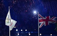 The Union Flag (R) flies next to the Olympic flag (L) during the opening ceremony of the London 2012 Olympic Games at the Olympic Stadium in London on July 27, 2012.  AFP PHOTO / CHRISTOPHE SIMON