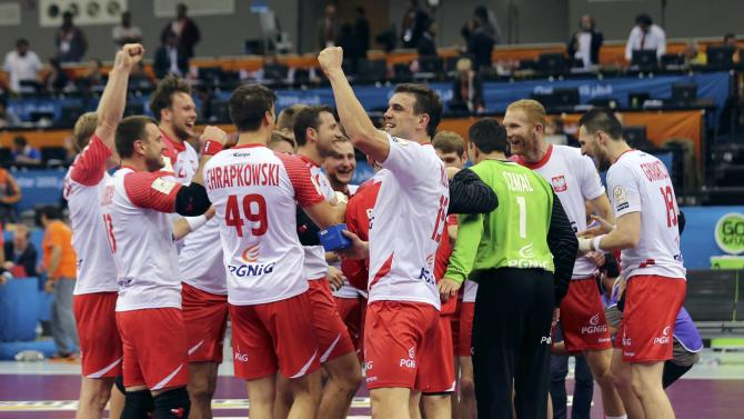 Poland's players celebrate after their round of 16 match against Sweden during the 24th men's handball World Championship in Doha