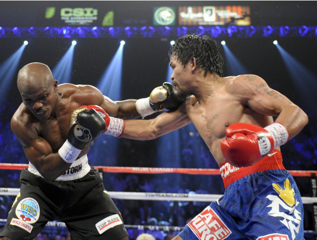 Timothy Bradley, from Palm Springs, Calif., left, trades blows with Manny Pacquiao, from the Philippines, in their WBO world welterweight title fight Saturday, June 9, 2012, in Las Vegas. Bradley won