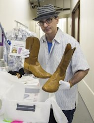"In this Friday, Nov. 30, 2012 photo, James Comisar shows boots worn by actor Larry Hagman as oil tycoon J. R. Ewing in the TV show ""Dallas."" The item is part of his television memorabilia collection in a temperature- and humidity-controlled warehouse in Los Angeles. (AP Photo/Damian Dovarganes)"