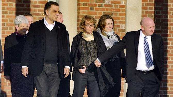 FILE - Former U.S. Rep. Gabrielle Giffords, center, holds hands with her husband, Mark Kelly, while exiting Town Hall at Fairfield Hills Campus in Newtown, Conn. after meeting with Newtown  officials in this Jan. 4, 2013 file photo.  Giffords also met with families of the victims of the Sandy Hook Elementary massacre that left 26 people dead. Tuesday Jan. 8, 2013 is the second anniversary of the shooting of Giffords. Tucson will mark the anniversary by ringing bells across the city at the moment that Jared Lee Loughner opened fire at a supermarket where Giffords was meeting with constituents.(AP Photo/The News-Times, Jason Rearick) MANDATORY CREDIT