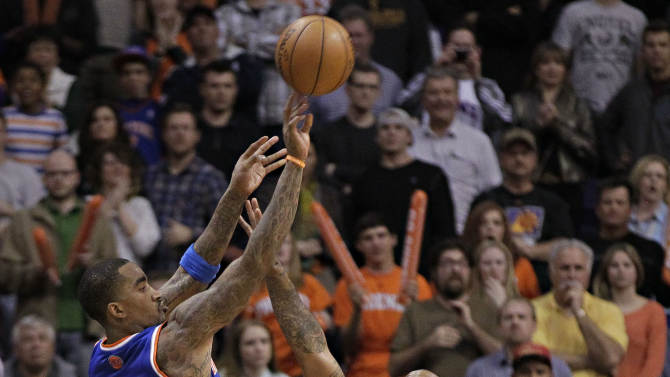 New York Knicks' J.R. Smith (9) takes the game-winning shot over Phoenix Suns' P.J. Tucker (17) during the second half of an NBA basketball game, Wednesday, Dec. 26, 2012, in Phoenix. The Knicks won 99-97. (AP Photo/Matt York)