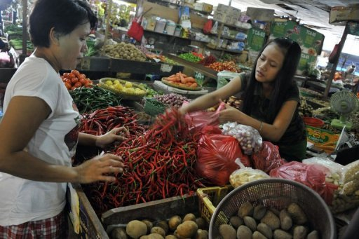 A customer buys chillies at a market in Jakarta