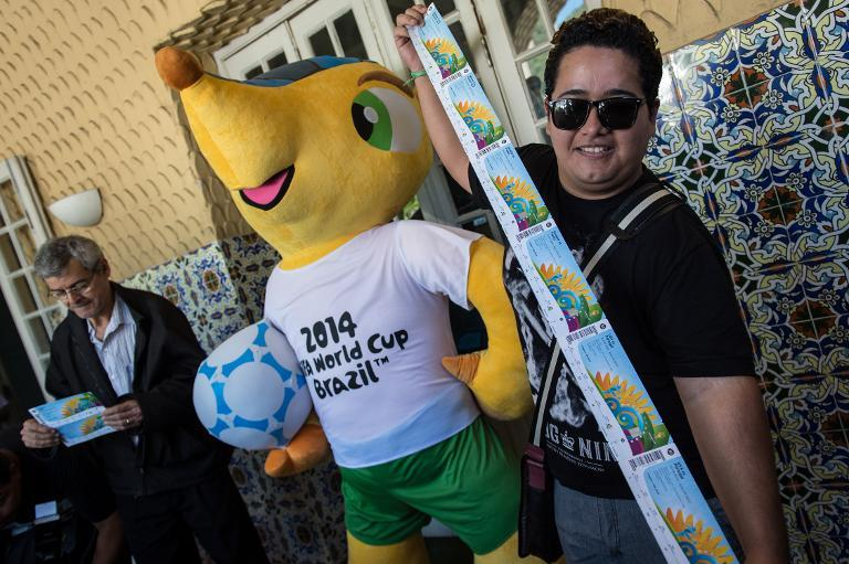 Football fans Joao Bosco (L) and Vanderson Balbino pose with the FIFA World Cup Brazil 2014 mascot as they show the tickets for the tournament on April 18, 2014, at the Botafogo club in Rio de Janeiro