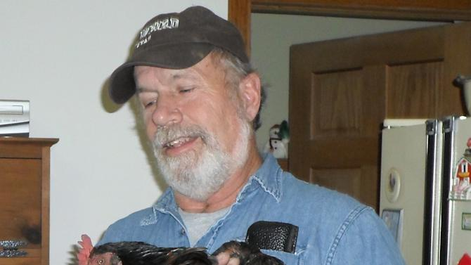 In this photo provided by Barb Murray, Brad Krueger of Alma Center, Wis., holds his neighbors' chicken, Cluck Cluck, on Friday, Dec. 28, 2012. The chicken, which the neighbors kept as a pet, is being credited for saving that family from an early-morning fire Thursday by waking the couple with its vocal clucking. (AP Photo/Courtesy Barb Murray)