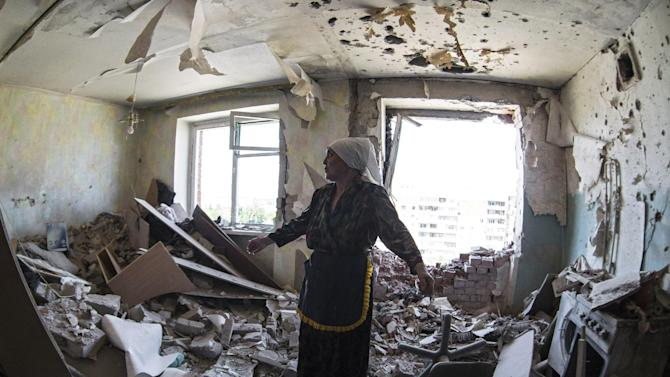 Valentina, who gave only her first name, gestures in a flat of her neighbor who was injured during shelling in the city of Kramatorsk, Donetsk region, eastern Ukraine, Thursday, July 3, 2014. Residential areas came under shelling on Thursday from government forces. (AP Photo/Dmitry Lovetsky)