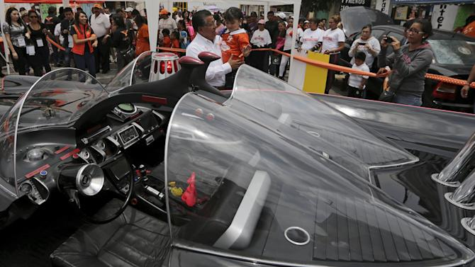 Valentin Gonzalez, mayoral candidate for the Citizen's Movement Party, carries a girl while standing next to a Batmobile replica in Nezahualcoyotl
