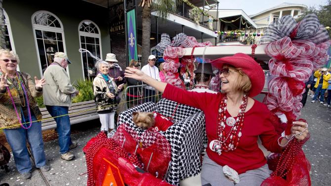 Lynn Lake throws beads as she and her dog, Lillie, particpate in the 10th Annaul Mardi Gras Dog Parade held Sandestin Resort's Village at Baytowne Wharf in Destin, Fla. Sunday, Feb. 10, 2013. Hundreds of spectators lined the streets to see the well dressed canines and catch throws ranging from beads to dog biscuits in the annual parade, which is a fundraiser for the Alaqua Animal Refuge. (AP Photo/Northwest Florida Daily, Devon Ravine)