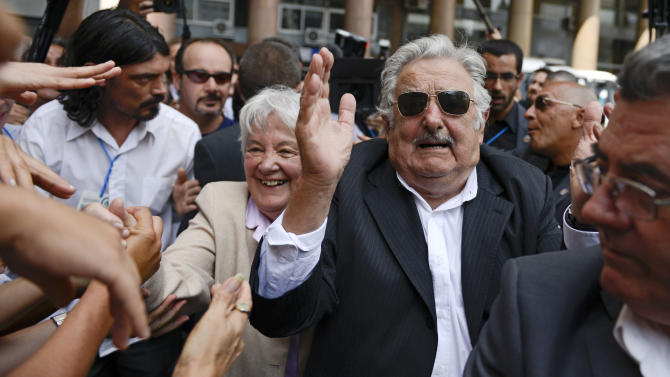 Uruguay's former President Jose Mujica and wife Lucia Topolansky greet supporters after the swearing-in ceremony for Uruguay's new President Tabare Vazquez at Independence Plaza in Montevideo, Uruguay, Sunday, March 1, 2015. (AP Photo/Matilde Campodonico)