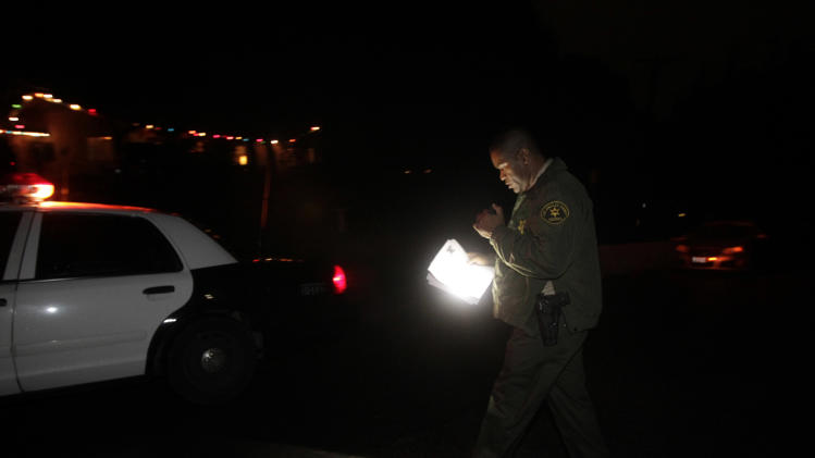 Los Angeles County Sheriff's deputy Cope, who only gave his last name, uses a flashlight while reviewing a waiver signed by a resident in La Canada Flintridge, Calif., Tuesday, Dec. 21, 2010. Forecasters expected heavy rains across California going into Wednesday, and authorities began evacuations late Tuesday as concern grew about potential mudslides in the wildfire-scarred foothills across the southern part of the state. (AP Photo/Jae C. Hong)