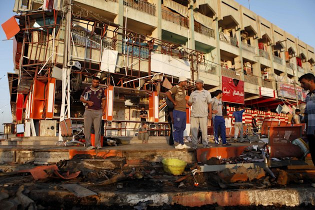 People inspect the aftermath of an overnight car bomb attack in Baghdad's Shiite enclave of Sadr City, Iraq, Friday, Aug. 17, 2012. Iraqi officials said Friday that a blistering string of attacks across the country the previous day ultimately killed scores of people, as the extent of the violence grew clearer and mourners started to bury their dead.(AP Photo/Karim Kadim)