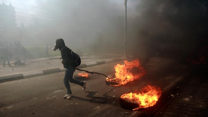 A man burns tires during a protest to support Palestinian prisoners, outside Ofer, an Israeli military prison, near the West Bank city of Ramallah, Monday, Feb. 25, 2013. The fate of the prisoners is sensitive in Palestinian society, where virtually every family has had a member imprisoned by Israel. Detainees are held on a range of charges, from stone-throwing to deadly attacks, and are seen as heroes resisting occupation. Israelis tend to view them as terrorists. (AP Photo/Majdi Mohammed)