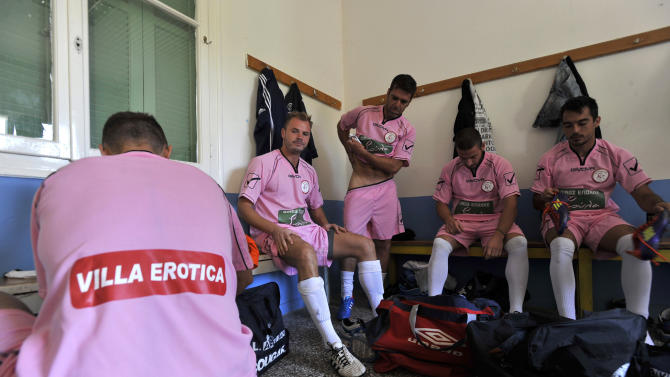 In this photo taken Sunday, Oct. 7, 2012, Voukefalas players, a small amateur soccer club, get ready in a changing room before a local championship match in the city of Larissa, central Greece.  A cash-strapped Greek soccer team has found a new way to pay the bills, with help from the world's oldest profession. Players are wearing bright pink practice jerseys emblazoned with the logos of the Villa Erotica and Soula's House of History, a pair of pastel-colored bordellos recruited to sponsor the team after drastic government spending cuts left the country's sports organizations facing ruin. One team took on a deal with a local funeral home and others have wooed kebab shops, a jam factory, and producers of Greece's trademark feta cheese. But the small amateur Voukefalas club which includes students, a bartender, waiters and pizza delivery drivers is getting the most attention for its flamboyant sponsors.   (AP Photo/Nikolas Giakoumidis)
