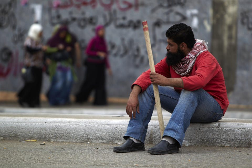 In this Monday, April 30, 2012 photo, a protester sitting on a sidewalk holds a stick in Cairo, Egypt.  Security officials say a protester has been killed when clashes erupted between unidentified assailants and demonstrators gathered outside the Defense Ministry in the Egyptian capital to call for an end to military rule. (AP Photo/Fredrik Persson)
