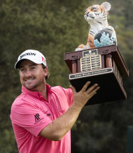 Graeme McDowell celebrates with the trophy after winning the World Challenge golf tournament at Sherwood Country Club in Thousand Oaks, Calif., Sunday, Dec. 2, 2012. (AP Photo/Bret Hartman)