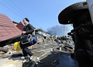 A local resident bring his son's school bags from a collaped house in Tagajo, Miyagi prefecture. Japan raced to avert a meltdown of two reactors at a quake-hit nuclear plant Monday as the death toll from the disaster on the ravaged northeast coast was forecast to exceed 10,000