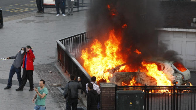 People pose for photos in front of a burning car set alight during the second night of civil disturbances in central Birmingham, England, Tuesday, Aug. 9, 2011. Britain began flooding London's streets with 16,000 police officers Tuesday, nearly tripling their presence as the nation feared its worst rioting in a generation would stretch into a fourth night. The violence has turned buildings into burnt out carcasses, triggered massive looting and spread to other U.K. cities.  (AP Photo/Tim Hales)