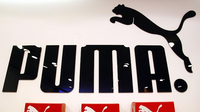 FILE - In this April 10, 2007 file photo, Puma sports shoes are displayed for sale in front of the company sign at a store in Munich, southern Germany. How big is your sneaker's carbon footprint? In a quest to find out, sportswear giant Puma's chairman, Jochem Zeitz, helped develop the Environmental Profit & Loss Account, or EP&L, a balance sheet that assigns a dollar figure to the environmental costs inflicted at every step of the manufacturing process that transforms rubber, cotton, leather and other materials into the brand's iconic soccer shoes, track suits and jerseys.  Proponents hope that assigning monetary values to resources will help put the brakes on unfettered development.  (AP Photo/Christof Stache, File)