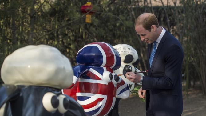 "Britain's Prince William, Duke of Cambridge, paints the eye of a ""Shaun the Sheep"" sculpture at the British Ambassador's official residence in Beijing"