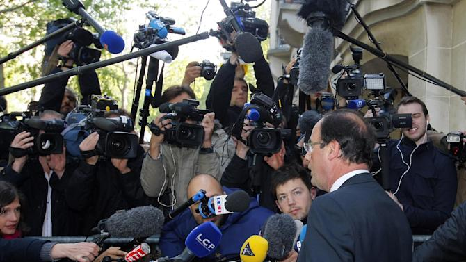 President-elect Francois Hollande answers questions of journalists as he arrives at the Socialist Party headquarters in Paris Monday May 7, 2012. France handed the presidency to leftist Hollande, a champion of government stimulus programs who says the state should protect the downtrodden, a victory that could deal a death blow to the drive for austerity that has been the hallmark of Europe in recent years. (AP Photo/Michel Spingler)