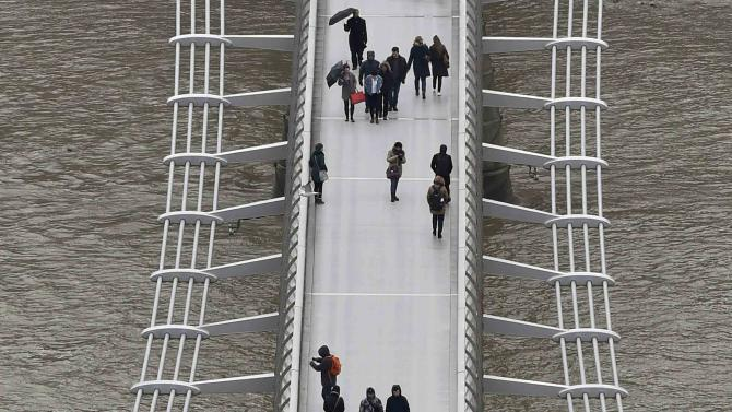 Pedestrians carry umbrellas as they walk across the London Millennium Bridge, over the River Thames, in London