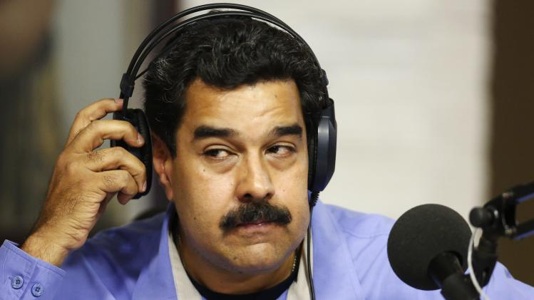 "Venezuela's President Maduro adjusts his headphones during his radio program ""In contact with Maduro"" in Caracas"