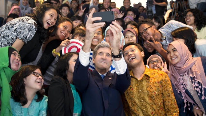 """Secretary of State John Kerry takes a selfie with a group of students before delivering a speech on climate change on Sunday, Feb. 16, 2014, in Jakarta, Indonesia. Climate change may be the world's """"most fearsome"""" weapon of mass destruction and urgent global action is needed to combat it, Kerry said on Sunday, comparing those who deny its existence or question its causes to people who insist the Earth is flat. (AP Photo/ Evan Vucci, Pool)"""