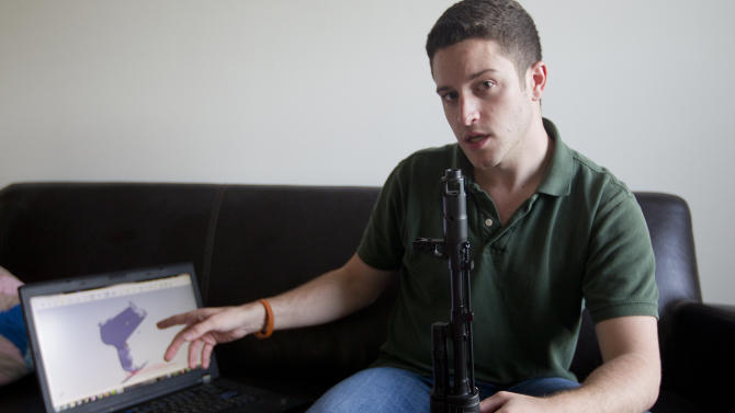 "In this Oct. 3, 2012 photo, ""Wiki Weapons"" project leader Cody Wilson points to his laptop screen displaying an image of a prototype plastic gun on the screen, while holding in his other a weapon he calls ""Invivdual Mandate,"" in Austin, Texas. At least one group, called Defense Distributed, is claiming to have created downloadable weapon parts that can be built using the increasingly popular new-generation of printer that utilizes plastics and other materials to create 3-D objects with moving parts. Wilson says the group last month test fired a semiautomatic AR-15 rifle _ one of the weapon types used in the Connecticut elementary school massacre _ which was built with some key parts created on a 3-D printer. The gun was fired six times before it broke. (AP Photo/Statesman.com, )  MAGS OUT; NO SALES; INTERNET AND TV MUST CREDIT PHOTOGRAPHER AND STATESMAN.COM"