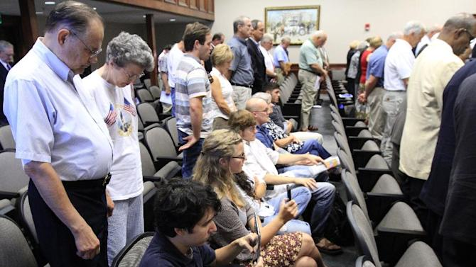 FILE - This June 20, 2012 file photo shows protesters remaining seated during an opening prayer during Hamilton County Commission meeting in Chattanooga, Tenn.  It happens every week at meetings in towns, counties and cities nationwide. A lawmaker or religious leader leads a prayer before officials begin the business of zoning changes, contract approvals and trash pickup. But citizens are increasingly taking issue with these prayers, some of which have been in place for decades. At least five lawsuits around the country — in California, Florida, Missouri, New York, and Tennessee — are actively challenging pre-meeting prayers. (AP Photo/Chattanooga Times Free Press, Dan Henry, File)