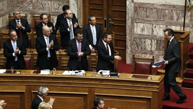 Lawmakers applaud Greek Prime Minister Samaras after his speech during a parliament session where lawmakers vote on the 2014 budget in Athens