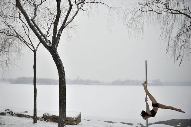 A member of China's national pole dance team performs at a park after the city's first snow this winter in Tianjin