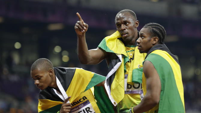 Jamaica's gold medal winner Usain Bolt, center, celebrates with his teammate Warren Weir, left, and Yohan Blake after the men's 200-meter final during the athletics in the Olympic Stadium at the 2012 Summer Olympics, London, Thursday, Aug. 9, 2012.  (AP Photo/Lee Jin-man)