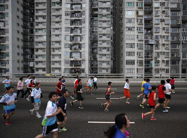 Participants run past high-rise residential apartments during a 10-kilometre race of the Hong Kong Marathon