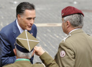 U.S. Republican presidential candidate, former Massachusetts Gov. Mitt Romney speaks with Polish WWII veterans after laying a wreath at the Warsaw 1944 Uprising monument in Warsaw, Poland, Tuesday, July 31, 2012. (AP Photo/Alik Keplicz)