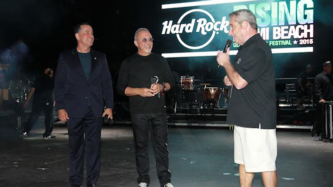 IMAGE DISTRIBUTED FOR HARD ROCK INTERNATIONAL - Mayor Phillip Levine of the City of Miami Beach and Jim Allen, CEO of Seminole Gaming and Chairman of Hard Rock International, pay tribute to Grammy-winning producer and musician Emilio Estefan on stage at the Hard Rock Rising Miami Beach global music festival on Thursday, March 26, 2015, in Miami Beach. (Photo credit: Hard Rock International/Ralph Notaro)