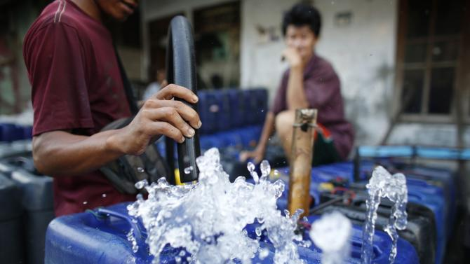 A man fills up his plastic containers with water in north Jakarta