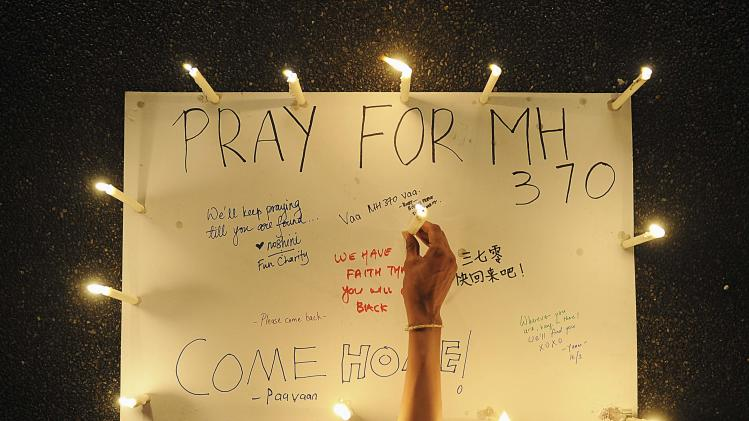 A woman places lighted candle on poster with messages expressing hope for passengers of missing Malaysia Airlines plane MH370 during a candlelight vigil in Petaling Jaya