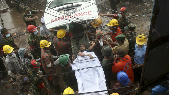 A survivor is carried on a stretcher into a waiting ambulance after being evacuated from a garment factory building that collapsed Wednesday in Savar, near Dhaka, Bangladesh, Saturday, April 27, 2013. Police in Bangladesh took five people into custody in connection with the collapse of a shoddily-constructed building this week, as rescue workers pulled 19 survivors out of the rubble on Saturday and vowed to continue as long as necessary to find others despite fading hopes.(AP Photo/Wong Maye-E)