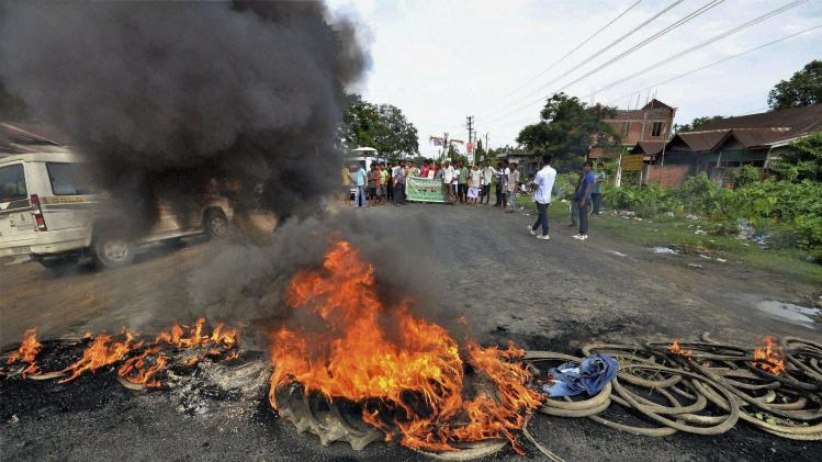 In this Wednesday, Aug. 20, 2014 photo, members of Asom Jatiyatabadi Yuva Chhatra Parishad (AJYCP) burn tires to block a road at Bokakhat in Golaghat, India. Army troops patrolled border districts of India's northeastern Assam state Thursday following sporadic violence that has left more than a dozen dead and over 10,000 displaced. Shops and businesses were closed in Golaghat town, where three people were killed after police opened fire to quell protests over attacks by tribespeople from neighboring Nagaland state, Assam's Home Secretary G. D. Tripathy said. (AP Photo/Press Trust of India) INDIA OUT