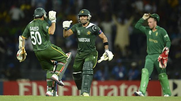 Pakistan's Umar Akmal and Saeed Ajmal (L) celebrate after winning the ICC World Twenty20 Super 8 cricket match as South Africa's AB de Villiers takes off his cap at the R Premadasa Stadium