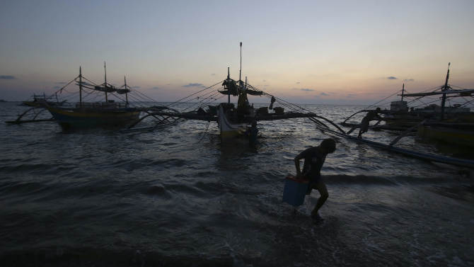In this May 7, 2013 photo, a Filipino boy carries a container from newly arriving fishing boats as the sun sets in the coastal town of Infanta, Pangasinan province, northwestern Philippines. Since China took control of the Scarborough Shoal last year, which Beijing calls Huangyan Island, Filipino fishermen say Chinese maritime surveillance ships have shooed them from the disputed waters in the South China Sea and roped off the entrance to the vast lagoon that had been their fishing paradise for decades. Now, they say, they can't even count on the Chinese to give them shelter there from a potentially deadly storm. (AP Photo/Aaron Favila)