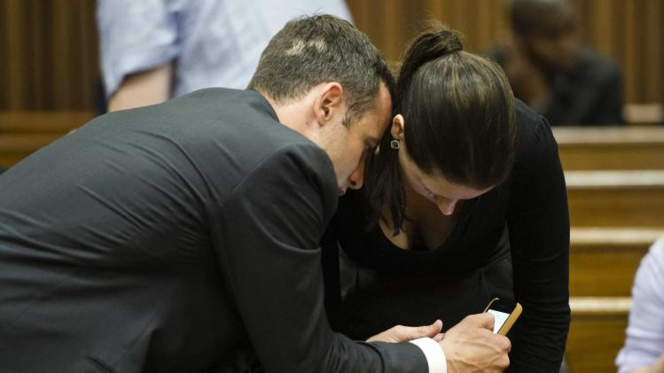 Pistorius looks at his mobile phone with his sister during the fifth day of his trial in Pretoria