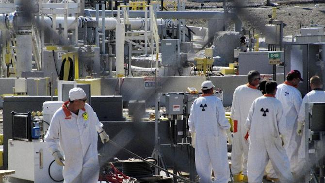 "FILE - In this July 14, 2010 photo, workers at the Hanford nuclear reservation work around a a tank farm where highly radioactive waste is stored underground near Richland, Wash. Six underground radioactive waste tanks at the nation's most contaminated nuclear site are leaking, Gov. Jay Inslee said Friday, Feb. 22, 2013. Inslee made the announcement after meeting with federal officials in Washington, D.C. Last week it was revealed that one of the 177 tanks at south-central Washington's Hanford Nuclear Reservation was leaking liquids. Inslee called the latest news ""disturbing."" (AP Photo/Shannon Dininny, File)"