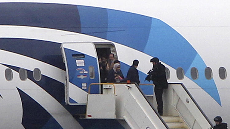 Passengers disembark from an Egyptair aircraft at Prestwick Airport, Scotland, after it was diverted while en route from Cairo to New York, Saturday June 15, 2013. It is reported that BBC employee Nada Tafik, who was on board the plane, said she found a note in a toilet apparently threatening to start a fire. The plane was escorted to Prestwick airport by Typhoon fighters from RAF Leuchars, near St. Andrews on the east coast of Scotland. (AP Photo/ Andrew Milligan /PA) UNITED KINGDOM OUT
