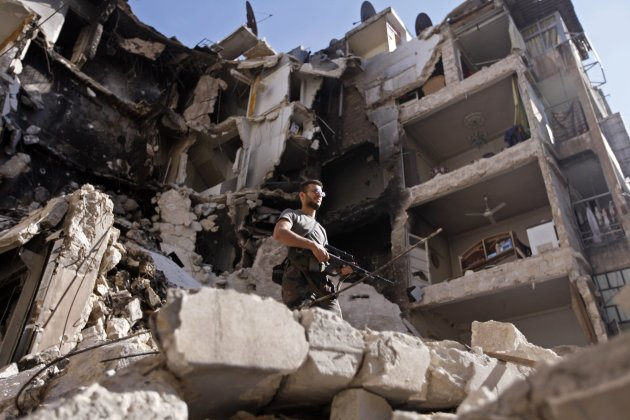 A member of the Free Syrian Army inspects damaged houses in Bustan al Basha in Aleppo city in northern Syria October 12, 2012. REUTERS/Zain Karam (SYRIA - Tags: CIVIL UNREST POLITICS)
