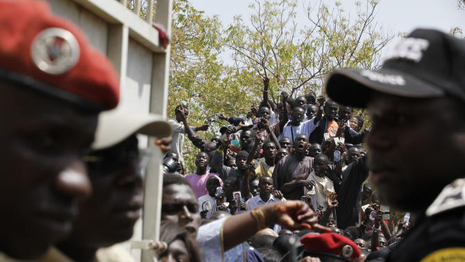Security forces stand guard at the entrance to the polling station where Senegalese President Abdoulaye Wade was due to vote, as supporters cheer in the street outside, in the Point E neighborhood of Dakar, Senegal Sunday, March 25, 2012. Senegalese voters are deciding Sunday whether to give their 85-year-old president another term in office, or instead back his one-time protege Macky Sall in a runoff election that could oust the incumbent of 12 years. (AP Photo/Rebecca Blackwell)