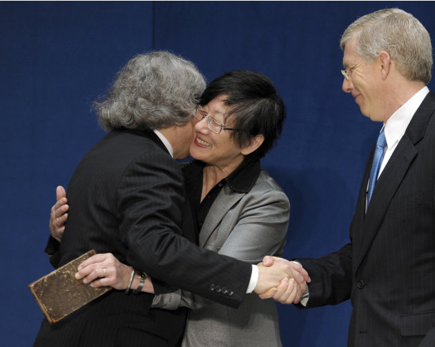 Dr. Ernest Moniz, left, hugs his wife Naomi, center, ad shakes hands with Deputy Energy Deputy Secretary Daniel Poneman, right, after Poneman administered the oath of office to Moniz as Energy Secreta