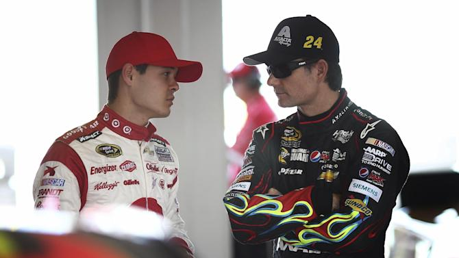 Drivers Kyle Larson, left, and Jeff Gordon talk during practice for Sunday's NASCAR Sprint Cup series auto race at the Homestead-Miami Speedway, Saturday, Nov. 16, 2013, in Homestead, Fla