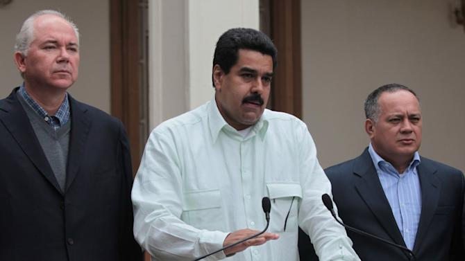 """In this photo released by Miraflores Press Office, Venezuela's Vice President Nicolas Maduro, center, addresses the nation on live television flanked by Oil Minister Rafael Ramirez, left, and National Assembly President Diosdado Cabello at Miraflores presidential palace in Caracas, Venezuela, Wednesday, Dec. 12, 2012.  Maduro said that Chavez will face a """"complex and hard"""" process after undergoing his fourth cancer-related operation in Cuba on Tuesday. Over the weekend, Chavez named Maduro as his chosen political heir. (AP Photo/Miraflores Press Office, Efrain Gonzalez)"""